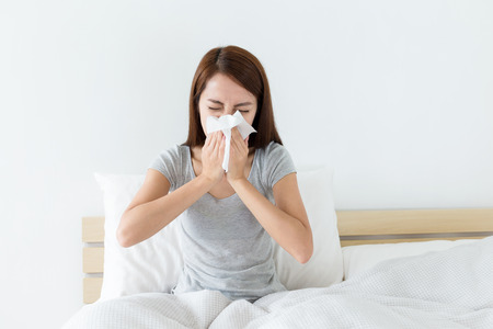 flu: Young woman sneeze on bed