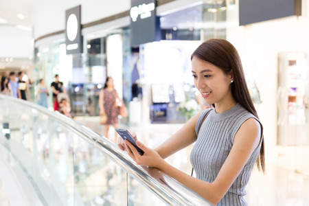 Young lady read the message on cellphone at department store