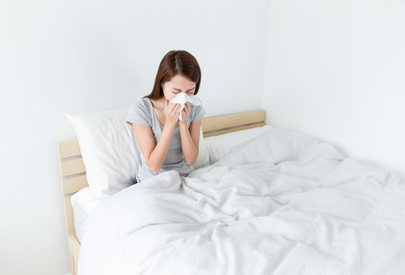 estornudo: Mujer estornudo en la cama Foto de archivo