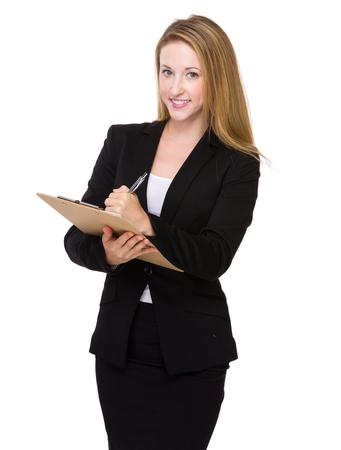Caucasian businesswoman take note on clipboard Stock Photo