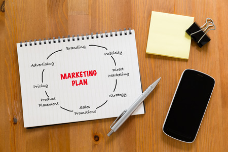 handbook: Working desk with mobile phone and handbook showing marketing planning