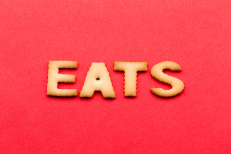 eats: Word eats biscuit over the red background