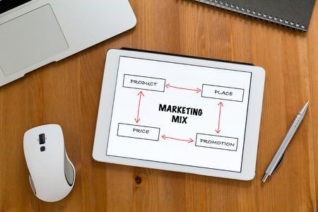 marketing mix: Modern working desk with tablet showing marketing mix concept