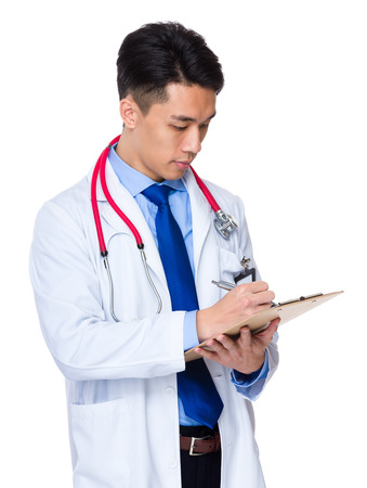 handsome doctor: Male doctor jotting down the case of patient