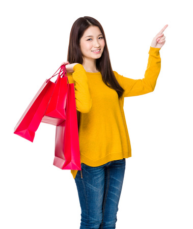 selling points: Young woman with shopping bag and finger point up