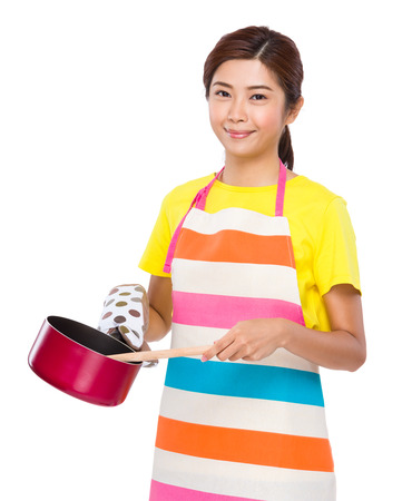 stockpot: Young Housewife cooking with saucepan