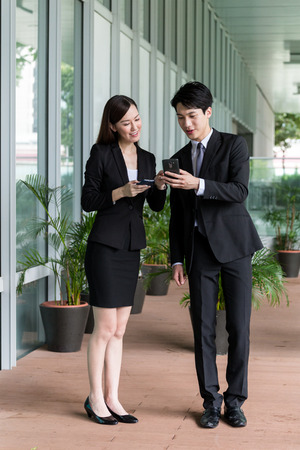discuss: Businesswoman discuss about something on cellphone with businessman Stock Photo