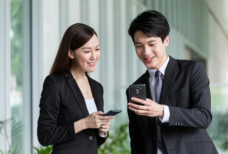 Geschäftspartner diskutieren Sie über den Details auf dem Smartphone Standard-Bild