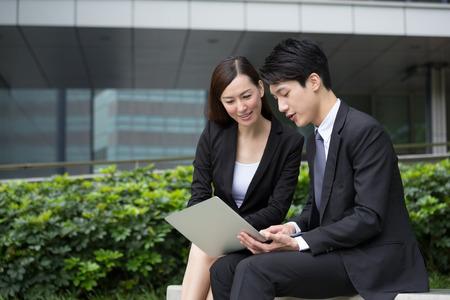 ビジネスマン ビジネスウーマンとノートブック コンピューター上で読む