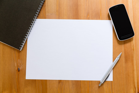adding: Empty White paper on desk with cellphone for adding information