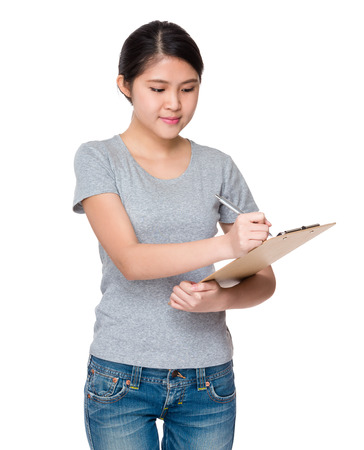 jot: Young student jot down the information on clipboard