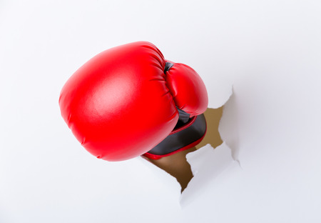 destroying the competition: Hand break through paper with boxing gloves
