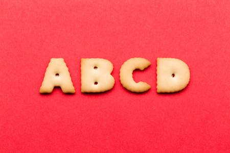 abcd: ABCD cookie over the red background Stock Photo