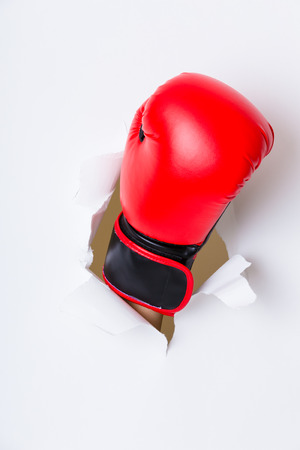 destroying the competition: Hand break through paper with red boxing gloves