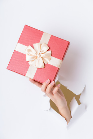 break: Hand break through paper with red gift box