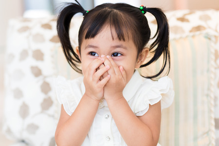 hands on mouth: Happy little girl with hand cover her mouth Stock Photo
