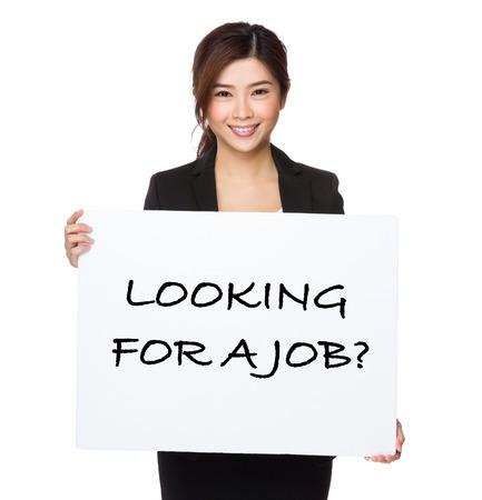 Mooie zakenvrouw met een poster met het zoeken naar een baan zinnen