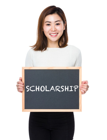 scholarship: Young woman with of blackboard showing a word scholarship