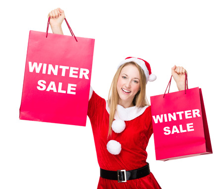 hold up: Woman with christmas party dress hold up with shopping bag and showing winter sale