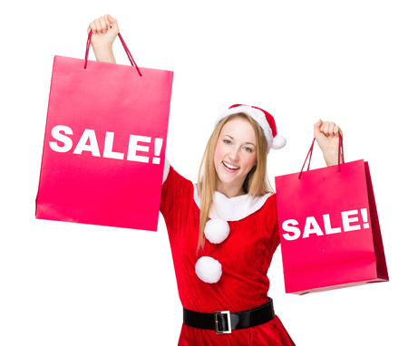 hold up: Woman with christmas party dress hold up with shopping bag and showing a word sale!