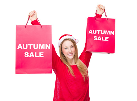 hold up: Woman with Christmas hat and hold up the paper bag showing autumn sale