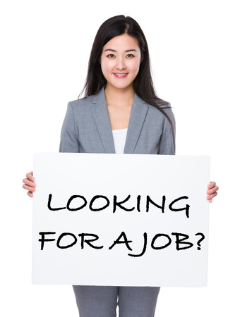 looking for job: Beautiful businesswoman holding a poster showing with looking for a job phrases Stock Photo