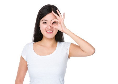ok sign: Asian woman with ok sign gesture on her eye