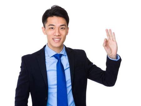 joyful businessman: Young businessman with ok sign gesture Stock Photo