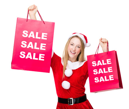 hold up: Woman with christmas party dress hold up with shopping bags and showing three sale word
