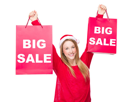 hold up: Woman with Christmas hat and hold up the paper bag showing big sale