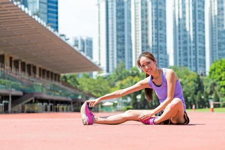 女性は屋外で脚のストレッチ運動