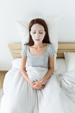 resting mask: Asian woman resting on bed and using paper mask