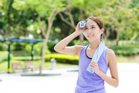 sudando: Mujer joven que usa la toalla azul después de hacer ejercicio del deporte