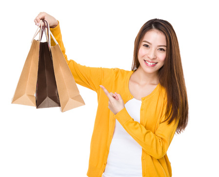 casual wear: Young woman finger point to shopping bag
