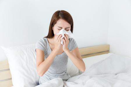 gripe: Sensaci�n de la mujer asi�tica mal y estornudar en la cama Foto de archivo