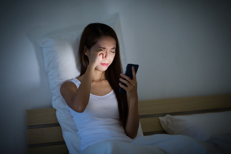 bed: Woman feeling eye painful with using cellphone on bed