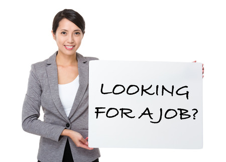 looking for job: Beautiful businesswoman showing a placard showing with looking for a job phrases Stock Photo
