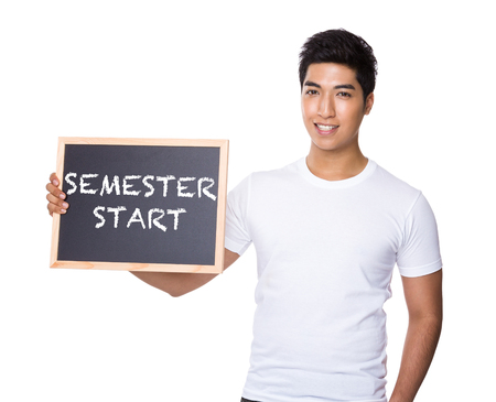 phrases: Asian man with chalkboard showing phrases of semester start Stock Photo