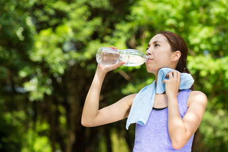 drinking water: Beautiful young asian woman drinking water after training