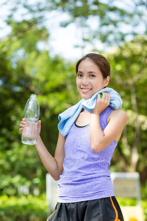 water sport: Fitness woman drinking water after running