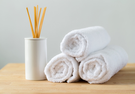 air diffuser: Aromatherapy reed diffuser air freshener with stack of white towel Stock Photo