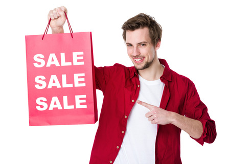 seasonal clothes: Happy shopping man with paper and showing three sale word