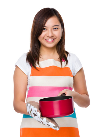 japanese cookery: Asian housewife using saucepan with oven glove Stock Photo