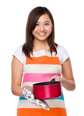 saucepan: Asian housewife using saucepan with oven glove Stock Photo