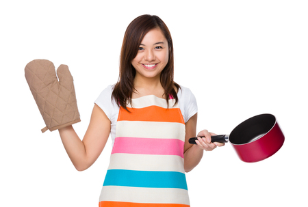 raise: Young housewife raise up with saucepan