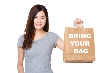 bring: Asian Woman hold with shopping bag for showing phrase of bring your bag