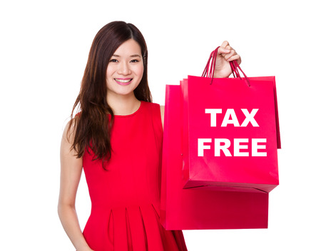 Woman hold with paper bag and showing tax free