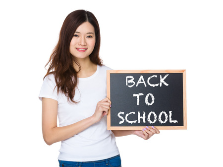 causal: Woman with the chalkboard showing phrase of back to school Stock Photo