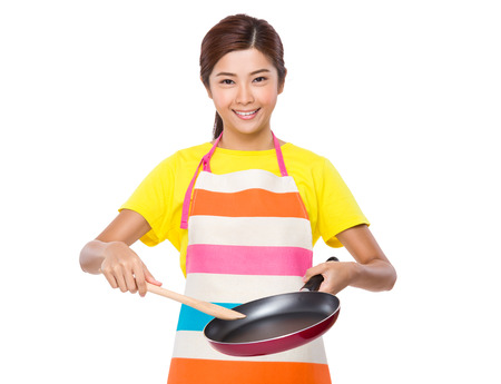pan asian: Asian housewife using the frying pan and wooden ladle