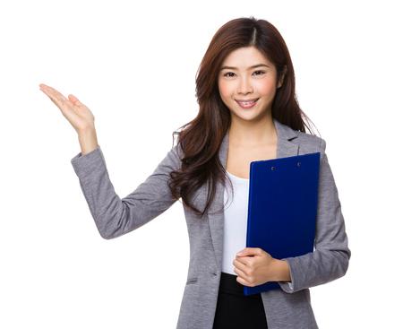 alzando la mano: Asian businesswoman hold with clipboard and open hand palm Foto de archivo